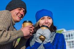 Paar die in de wintersweater koppen van koffie koesteren Stock Fotografie
