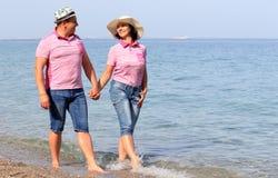 Paar die dichtbij het overzees lopen stock afbeelding