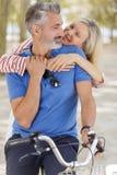 Paar die dichtbij moderne fiets in park koesteren stock fotografie