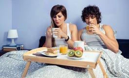 Paar die die ontbijt in bed hebben over dienblad wordt gediend Stock Foto