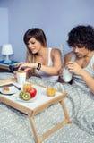 Paar die die ontbijt in bed hebben over dienblad wordt gediend Royalty-vrije Stock Foto
