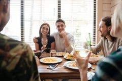 Paar die diner hebben en met vrienden op de keuken spreken stock fotografie