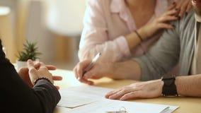 Paar die document, handenschuddenmakelaar in onroerend goed ondertekenen, die sleutels van nieuw huis krijgen stock footage