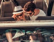 Paar die door auto reizen stock afbeeldingen