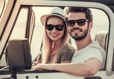 Paar die door auto reizen stock foto's
