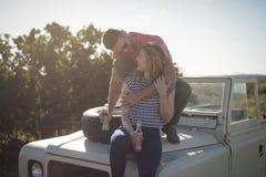 Paar die dranken op de bonnet van auto hebben royalty-vrije stock afbeelding