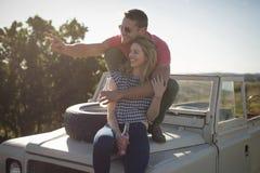 Paar die dranken op de bonnet van auto hebben royalty-vrije stock afbeeldingen