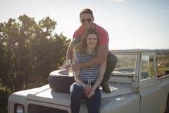 Paar die dranken op de bonnet van auto hebben stock afbeeldingen