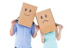 Paar die droevige gezichtsdozen op hun hoofden dragen Royalty-vrije Stock Foto