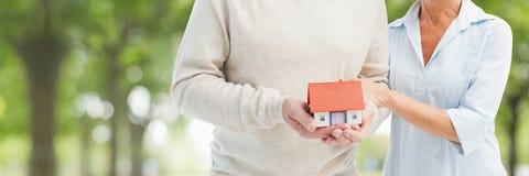 Paar die een huis houden tegen groene achtergrond als concept verzekering stock afbeeldingen