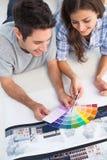 Paar die een kleurengrafiek bekijken om hun huis te verfraaien Stock Foto's