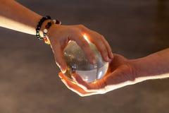 Paar die een kristallen bol samen houden stock foto