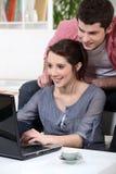 Paar die een laptop computer met behulp van Royalty-vrije Stock Foto's