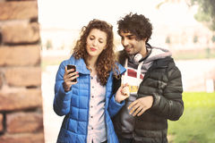 Paar die een mobiele telefoon en het luisteren muziek bekijken Stock Foto's