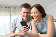 Paar die een mobiele telefoon thuis raadplegen stock foto's