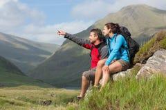 Paar die een onderbreking na wandeling bergop met mens het richten nemen Stock Foto