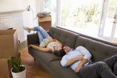 Paar die een Onderbreking op Sofa During Moving In Day nemen royalty-vrije stock afbeelding