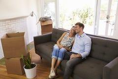 Paar die een Onderbreking op Sofa During Moving In Day nemen stock afbeeldingen