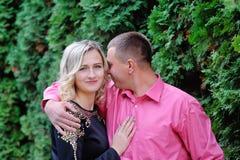 Paar die in een park gezet in een bank koesteren Royalty-vrije Stock Fotografie
