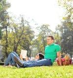 Paar die een picknick op aardige zonnige dag in park hebben Royalty-vrije Stock Afbeeldingen