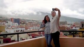Paar die een selfie doen bij telefoon op dak van huis stock videobeelden