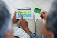 Paar die een tablet met e-lerende informatie in het scherm gebruiken stock foto
