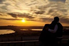 Paar die elkaar koesteren en op de zonsondergang letten Royalty-vrije Stock Foto