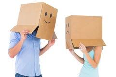 Paar die emoticon gezichtsdozen op hun hoofden dragen Royalty-vrije Stock Afbeeldingen