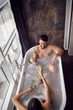 Paar die en in de badkuip en het drinken champagne hoogste mening genieten van ontspannen stock foto