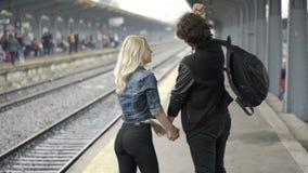 Paar die en hand in hand op station kussen lopen stock footage