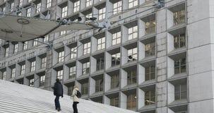 Paar die en La-Defensietreden en monument, Parijs, Frankrijk beklimmen bewonderen stock video