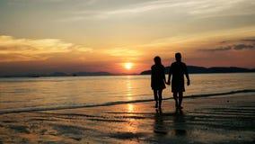 Paar die en op een tropisch strand bij zonsondergang kussen lopen stock videobeelden