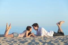 Paar die en op het strandzand dateren rusten Stock Foto