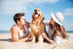 Paar die en pret met hond op het strand hebben liggen stock afbeelding