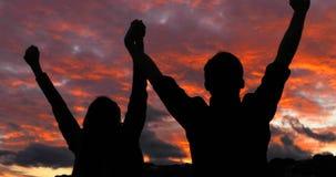 Paar die en wapens lopen opheffen bij zonsondergang stock footage
