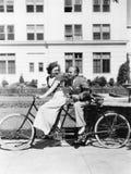 Paar die fiets achter elkaar berijden (Alle afgeschilderde personen leven niet langer en geen landgoed bestaat Leveranciersgarant stock fotografie