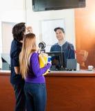 Paar die Filmprogramma controleren op Bespreekbureau stock foto's