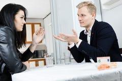 Paar die financiële crisis samen op lijst in keuken oplossen die - gesticuleren stock foto's