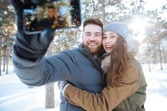 Paar die foto op smartphone in de winterpark maken Stock Foto's