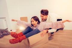 Paar die gek na het uitpakken van dozen met kleren gaan stock fotografie