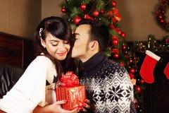 Paar die giften ruilen bij Kerstmis stock afbeelding