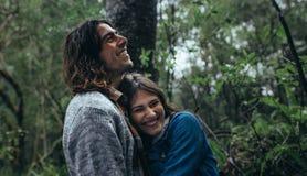 Paar die grote tijd in bos hebben tijdens regen stock foto's