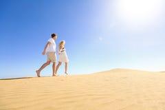 Paar die hebbend de handen van de pretholding onder zon lopen Royalty-vrije Stock Foto