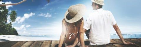 Paar die het Houten Concept van de Hemelwittebroodsweken van het Vloerstrand zitten stock foto