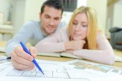 Paar die huisplannen bekijken stock afbeelding