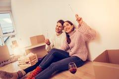 Paar die hun bewegende het drinken wijn vieren en het in brand steken van sterretjes royalty-vrije stock afbeeldingen