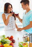 Paar die hun glazen rode wijn in de keuken clinking Stock Foto