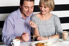 Paar die hun maaltijd verheugen zich in voedselhof Stock Afbeeldingen