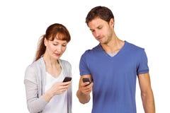 Paar die hun mobiele telefoons met behulp van Stock Fotografie