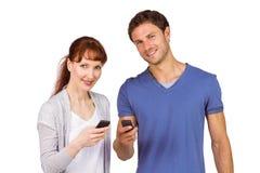 Paar die hun mobiele telefoons met behulp van Royalty-vrije Stock Afbeeldingen